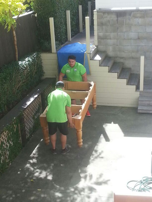 two men lifting a pool table in auckland