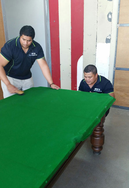 Two people safely moving the pool table