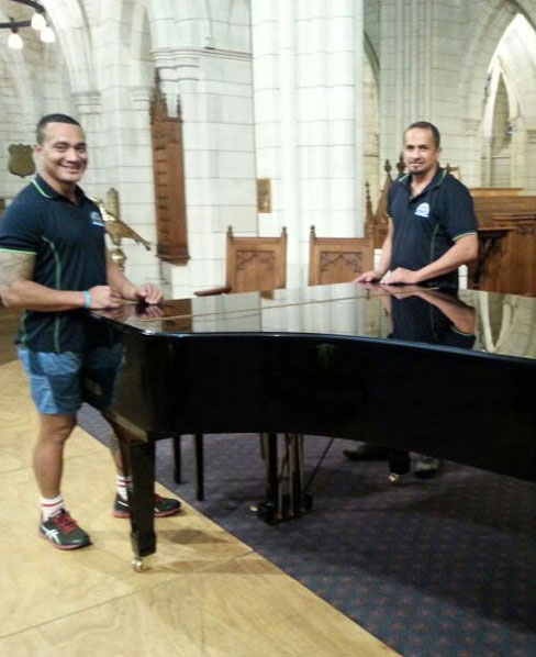 Two men ready to move a piano from an Auckland church