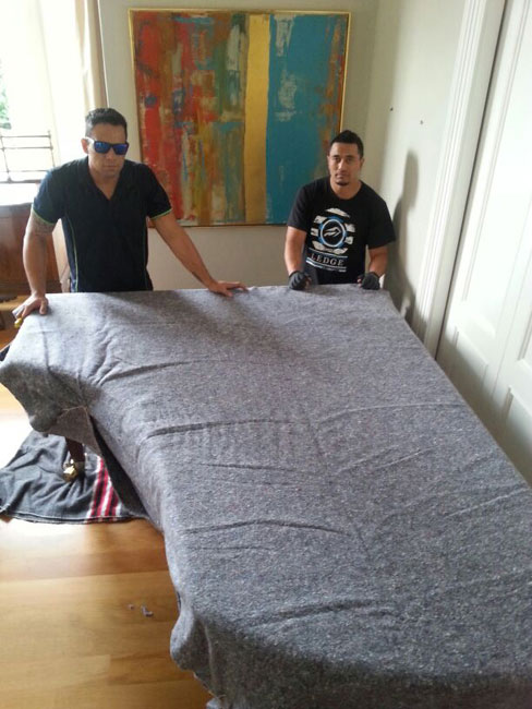 Two Auckland men wrapping a piano to move it safely