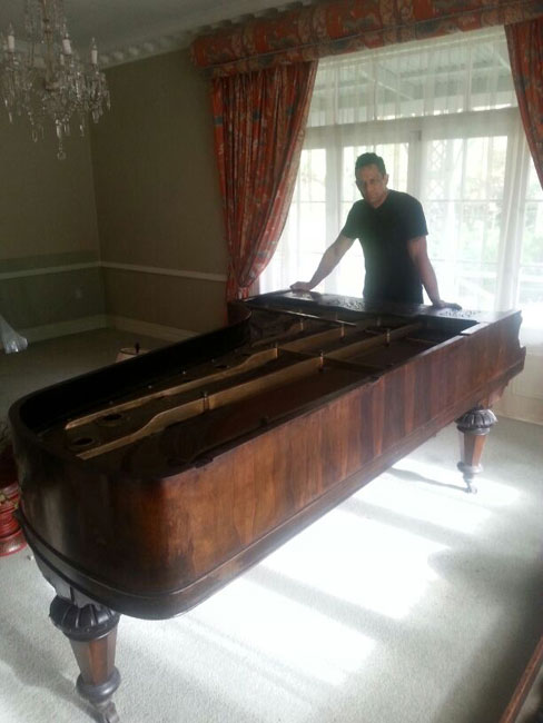 A Man moving a piano in Auckland